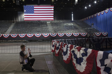 U.S. flag is seen in background as attendee photographs main stage at McCormick Place, during U.S. presidential election in Chicago