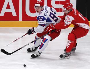 Denmark's Starkov covers Russia's Kuznetsov during their 2012 IIHF men's ice hockey World Championship game in Stockholm