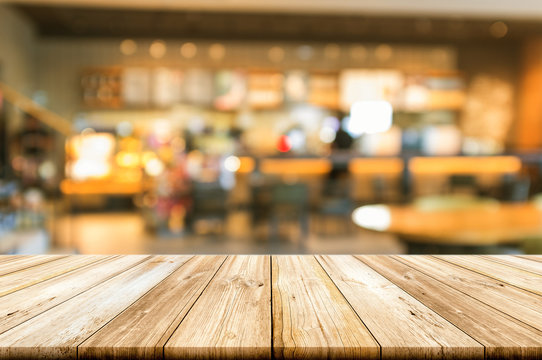 Empty wooden table top with blurred coffee shop interior background.