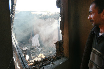 A local resident stands in his burned down house in the settlement of Mayevka outside Bishkek