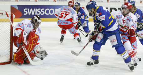 Duca of HC Davos challenges Spartak Moscow's Yakhin during their ice hockey match at the Spengler Cup tournament in the Swiss mountain resort of Davos