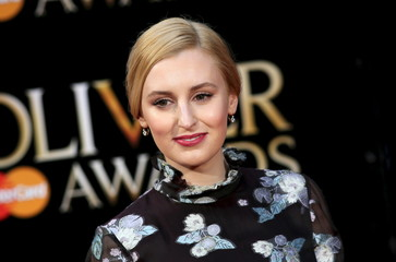 British actress Laura Carmichael poses for photographers as she arrives at the Olivier Awards at the Royal Opera House in London
