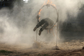 A rebel fighter jumps through a hoop of fire as he demonstrates his skills during a military display as part of a graduating ceremony at a camp in eastern al-Ghouta, near Damascus