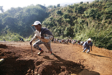 People look for precious stones in the mine dump piled by major mining companies at a jade mine in Pharkant township