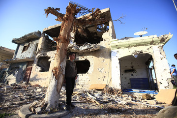 A boy stands by a house destroyed in battles between rebels fighters and forces loyal to Muammar Gaddafi on Tripoli street in central Misrata