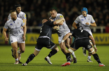Bath's Tom Dunn is tackled by Newcastle Falcons' Scott Lawson and Will Welch