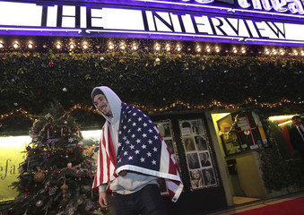 """Longshore draped in an American flag stands outside the Silent Movie Theatre for a midnight screening of """"The Interview"""" in Los Angeles"""