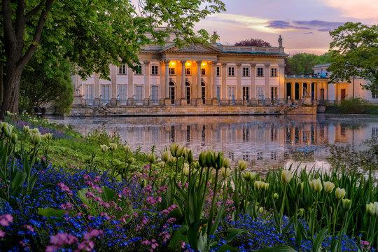 Pałac na Wyspie - Łazienki Królewskie. A Neoclassicist palace in Warsaw with a lot of flowers in spring.