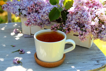 чашка чая с букетом сирени на старом стуле в саду