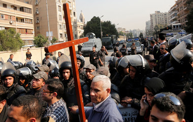 Egyptian Christians react in front of riot police outside the Virgin Mary church to get in the funeral for victims killed in the bombing of Cairo's main Coptic cathedral, in Cairo, Egypt
