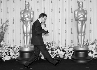 "French director Michel Hazanavicius, best director winner for his film ""The Artist,"" carries his Oscar in the photo room backstage at the 84th Academy Awards in Hollywood"