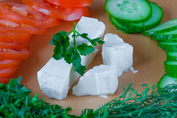 Closeup feta cheese with vegetables and herbs (ingredients for salad)