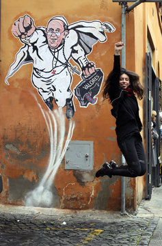 A woman jumps as a friend takes a photo in front of a large drawing of Pope Francis depicting him as a superhero near the Vatican