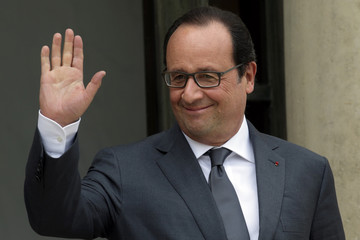 French President Francois Hollande waves from the steps of the Elysee Palace in Paris