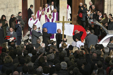 Mourners applaud to show their respect as the flag-draped coffin of late French politician Freche leaves the Saint Pierre Cathedral after services in Montpellier
