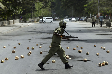 Riot policeman runs across a street in front of a coconut barricade placed there by protestors during a riot in Zanzibar