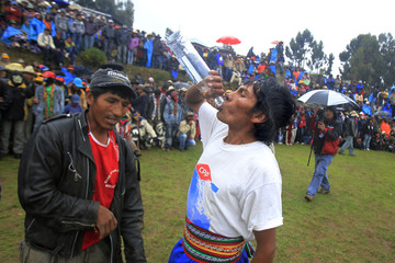 """An Andean man drinks a bottle of alcohol before fighting during the """"Takanakuy"""", a traditional festivity in Cuzco"""