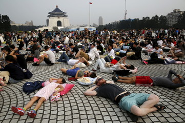 Participants rest during a break at the International Pillow Fight Day at Liberty Square, in Taipei