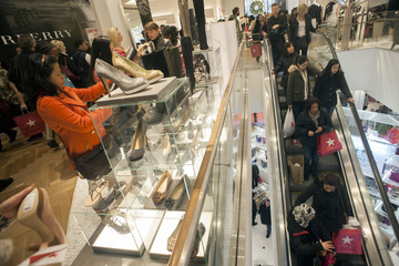 Shoppers look over shoes on sale at a Macy's store in New York