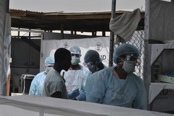 Health workers enter an Ebola treatment center in Monrovia