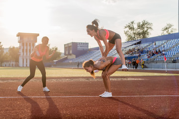 Fit women in the stadium playing leap frog.