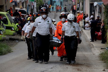 Rescue team members carry the body of a mudslide victim towards a temporary morgue, in Santa Catarina Pinula, on the outskirts of Guatemala City