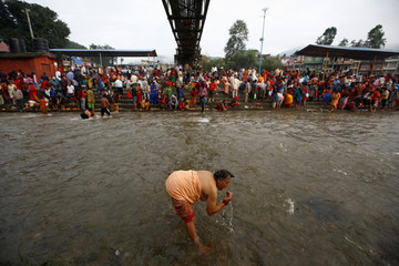 A Hindu devotee performs ritual on the Bagmati River during Kuse Aunse (Father's Day) at Gokarna Temple in Kathmandu