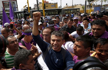 "Peru's ""Todos por el Peru"" (All for Peru) party presidential candidate Julio Guzman greets supporters after spending a night in vigil outside Peru's electoral board in Lima"