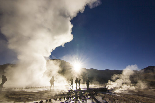 steam of geyser tatio against sun at sunrise with people standing