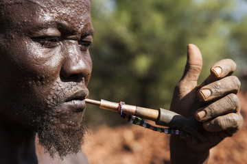 A Toposa man smokes his pipe as he takes a break at an excavation site for gold in Namorinyang