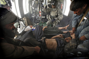 Crew chief Sgt Hara gives directions as an Afghan man and boy with gunshot wounds are loaded onto a medevac helicopter in Helmand Province