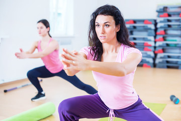 Fit women doing side lunges, exercises for legs, hips and buttocks.