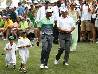 U.S. golfer Woods chats with compatriot O'Meara as he walks up the first fairway with his children Sam and Charlie and girlfriend Vonn during the par 3 event held ahead of the 2015 Masters at Augusta National Golf Course in Augusta
