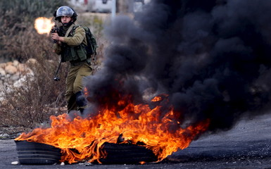 Israeli soldier fires a weapon towards Palestinian protesters during clashes near the Jewish settlement of Bet El, near the West Bank city of Ramallah
