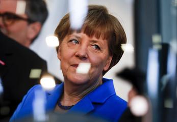German Chancellor Angela Merkel is seen through a window during her visit at the International Trade Fair in Munich