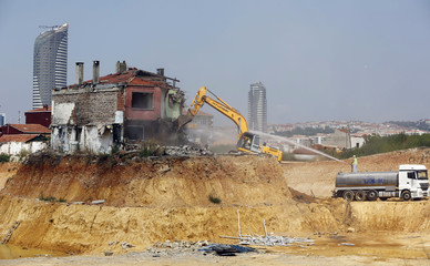 An excavator demolishes a lone house at the construction site of an urban transformation project in Fikirtepe