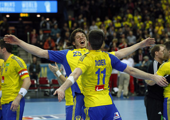 Sweden players celebrate after defeating Poland in their Group D match at Men's Handball World Championship in Gothenburg