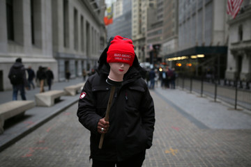 """A man sells hats reading """"Make America Great Again"""" outside the New York Stock Exchange prior to the inauguration of U.S. President-elect Donald Trump, in Manhattan, New York City"""