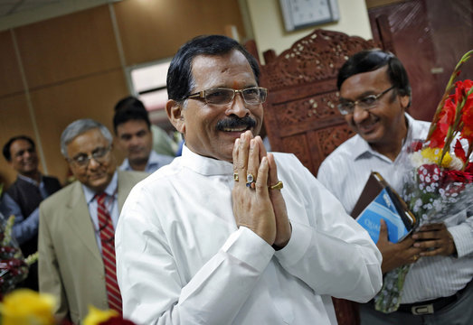Shripad Naik, India's new minister in charge of the department of AYUSH, greets the media as he arrives to take charge of his office in New Delhi