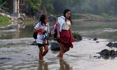 Girls walk on a shallow river to attend the opening of classes at a remote Casili Elementary School in Montalban, Rizal northeast of Manila