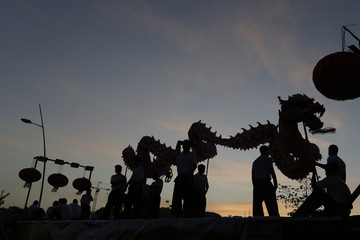 A dragon dance troupe is silhouetted during the last day of the annual Carnival parade in Panama City