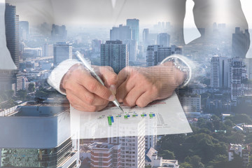 Double exposure of businessman hand hold a pen point to the bar graph, cityscape and urban in the foggy morning as Business, commitment and analysis concept