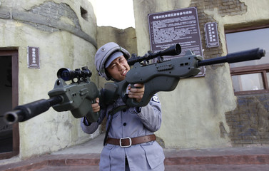 A man dressed as an Eighth Route Army soldier checks toy weapons before a live action role-playing game at a guerrilla warfare experiential park, on the outskirts of Wuxiang county