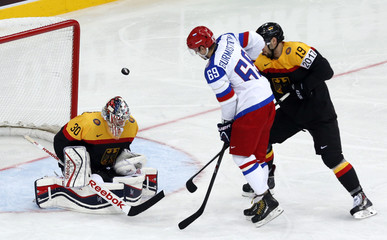 Russia's Burmistrov attempts to score between Germany's goalie Grubauer and Oppenheimer during the first period of their men's ice hockey World Championship Group B game at Minsk Arena in Minsk