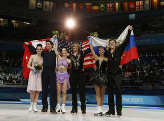 Skaters stand with their flags after the flower ceremony during the Figure Skating Ice Dance Free Dance Program at the Sochi 2014 Winter Olympics