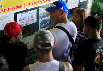 Stranded passengers gather at a ticketing booth with a note announcing the cancellation of bus trips due Typhoon Noul at a bus terminal in Manila