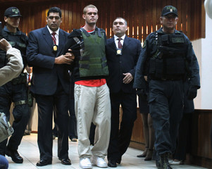 Joran Van der Sloot of the Netherlands is escorted by Peruvian police officers at the police headquarters in Lima