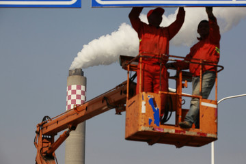 Workers install road signs in front of a port, as smoke rises from the chimney of a thermoelectric power plant in Shanghai