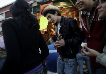 A man serenades a woman as she passes in front of the Basilica de Guadalupe in Guatemala City