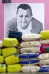 "Packages of rice are displayed in front of a picture of late French comic Coluche at a food distribution centre for the ""Les Restos du Coeur"" (Restaurants of the Heart) in Paris"